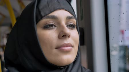 mulheres adultas meados : Face of young sweet muslim woman in hijab is watching in rainy window in bus, transport concept, urban concept, weather concept, dreaming concept