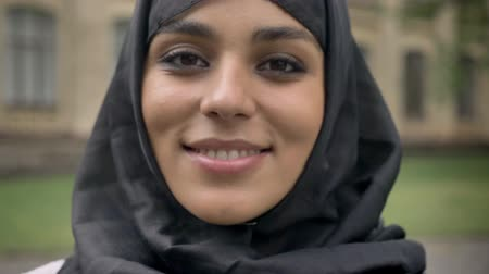 grey eyes : Young beautiful muslim girl in hijab turns her head to camera and smiling in daytime, in bad weather, religiuos concept, blurred background