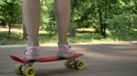кроссовки : Female legs riding on skateboard in park, asian female hipster on skate and holding backpack