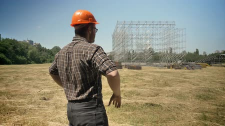 workman : Back of confident builder looking at metal construction on background, standing in helmet on straw field