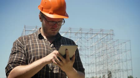 workman : Young architect using tablet and frowning, metal construction on background, serious