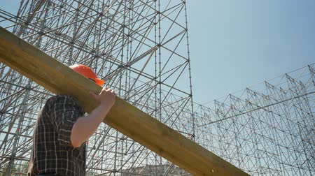 занятость : Young builder in helmet transferring heavy metal plank, working near huge metal installation