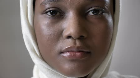 Пакистан : Face ofoung sad african muslim girl in hijab is looks up and watching at camera, religioun concept, grey background