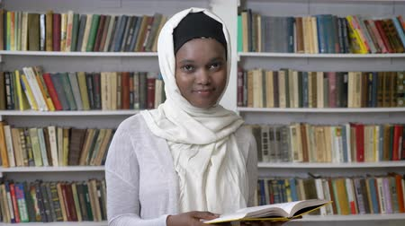 prateleira de livros : Young african muslim girl in hijab is holding book, watching at camera, religioun concept, booksheves on background