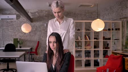 nuisance : Young blonde lesbian massaging woman in modern office during working, woman flirting with woman, seductive and attractive