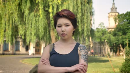 graduação : Portrait of young asian women with tattoo crossing hands and looking into camera in park near university, serious and concerned