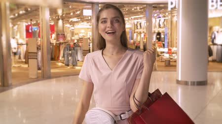 showcase : Young attractive girl goes shopping in mall, holds bags, laughing, like sign, shopping concept, fashion concept Stock Footage