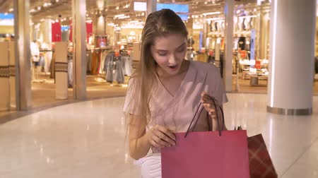 выражать : Young attractive girl goes shopping in mall, watches in bags, express surprise, shopping concept, fashion concept Стоковые видеозаписи