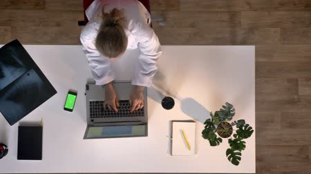 развертка : Young nurse in white coat typing on laptop, phone with chromakey lying on table, topshot, medical concept Стоковые видеозаписи