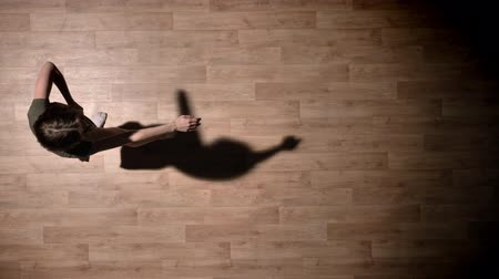 pirouette : Silhouette of young elegant girl is dancing on wooden floor, ballet concept, movement concept, top shot Stock Footage