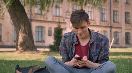 sms : Young handsome man is sitting on grass in park, tapping on smartphone, relax concept, communication concept, building on background