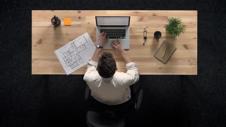 pracodawca : Young man is working on laptop, watches plan of building, in daytime, work concept, office concept, communication concept, top shot Wideo