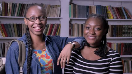 biblioteca : Two young african american female friends standing in library and smiling at camera, bookshelves background, happy