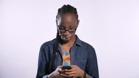 afro amerikan : Young african american woman in glasses typing on phone, isolated over white background, serious and concentrated Stok Video