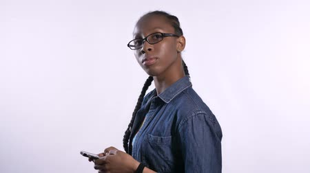 zsinórra : Young beautiful african american woman in glasses texting on phone and looking at camera, profile of black model in studio with phone, serious