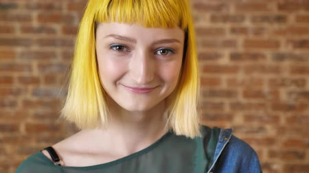 rendkívüli : Young shy woman with yellow hair looking at camera and smiling, brick wall background, cheerful and happy Stock mozgókép