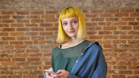 rendkívüli : Young pretty woman with yellow hairstyle typing on phone and smiling at camera, standing near brick background, happy and cheerful Stock mozgókép