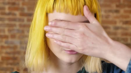 rendkívüli : Portrait of young woman with yellow hair looking at camera and moving her hands around her face, brick wall background