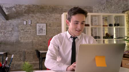 gidermek : Young businessman is working with laptop in office, happy because of good news, keeping hand fist, gesture concept, business concept, communication concept Stok Video