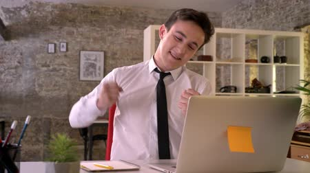 gidermek : Young businessman is working with laptop in office, happy because of business victory, keeping hand fist, gesture concept, communication concept