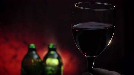 cheers : Mans hand holding and waving glass with red wine in slow motion shooting, two bottles and dark red background Stock Footage