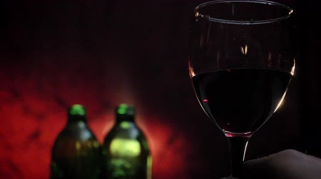 аперитив : Mans hand holding and waving glass of red wine in slow motion, two bottles and dark red background