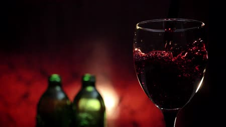 crimson : Pouring red wine in goblet, liquid splashing everywhere, two bottles and crimson background, 4k video
