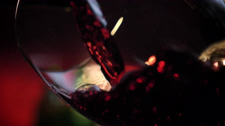 tasting : Close footage of red wine pouring into glass, alcohol drink splashing everywhere, dark background
