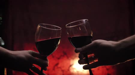 winogrona : Woman and man make toast with red wine, romantic dark red background, couple during date concept