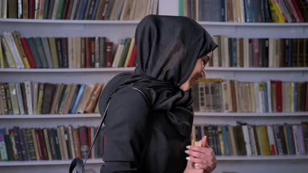 alfabetização : Young beautiful muslim girl in hijab is holding book, watching at camera, smiling, bookshelf on background, religious concept