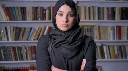 gramotnost : Young beautiful muslim girl in hijab crosses arms, watching at camera, religious concept, bookshelf on background Dostupné videozáznamy