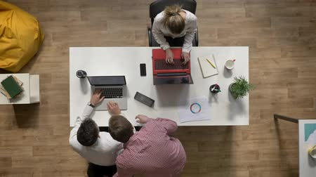 eladás : Two business men talking over laptop when woman working and sitting at table in modern office, topshot, work concept