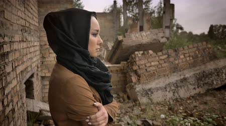 libya : Young muslim woman in hijab standing near ruined building and looking at camera with scared and worried expression, ruin in background Stock Footage