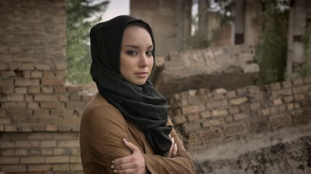 göçmen : Young refugee muslim woman in hijab standing near ruined building and looking at camera with frightened and scared expression during war