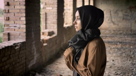 cold war : Young beautiful muslim woman in black hijab standing in abandoned building and looking at camera with scared and terrified expression