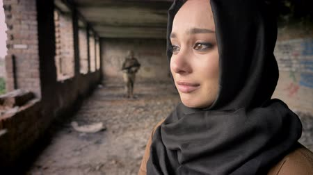 солдаты : Young sad muslim woman in hijab crying when armed soldier going towards woman, abandoned building, war concept