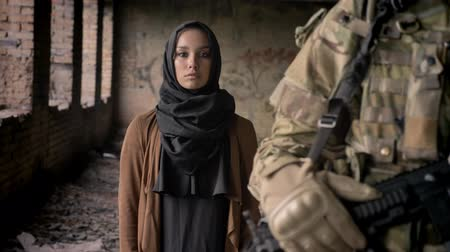 isis : Young muslim woman in hijab standing behind armed soldier with weapon and looking at camera with sad look, war concept