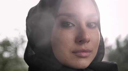pranto : Portrait of young sad muslim woman in hijab looking at camera and crying, rainy weather in background Stock Footage
