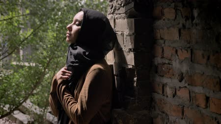 cold war : Young muslim woman in black hijab holding her hands and looking upwards, standing in abandoned brick building Stock Footage