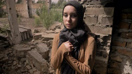 libya : Young muslim woman in hijab standing near ruined brick building and looking at camera, sad and depressed Stock Footage
