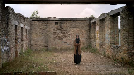 cold war : Young muslim woman in hijab standing alone in ruined abandoned brick building Stock Footage