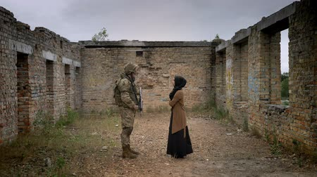 two forces : Armed soldier and young muslim woman in hijab standing inside ruined brick building and looking at each other, war concept