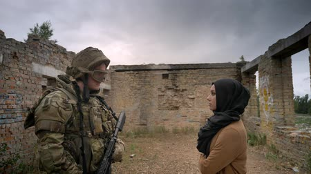 intruder : Young caucasian soldier and muslim woman in hijab standing inside brick ruined building and looking at each other, war concept Stock Footage
