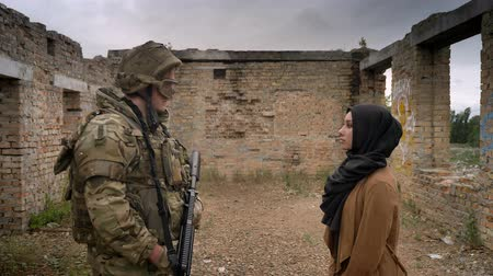 two forces : Young muslim woman in hijab looking at armed soldier with weapon and standing inside brick ruined house Stock Footage