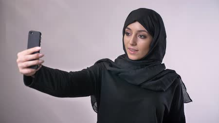 white cloths : Young beautiful muslim girl in hijab has a video call on smartphone, waving hello, communication concept, religious concept, grey background Stock Footage
