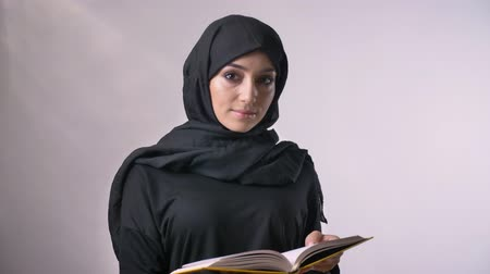alfabetização : Young sweet muslim girl in hijab is watching at camera and in book, religious concept, grey background Stock Footage