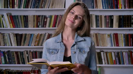 alfabetização : Young cute woman is reading book in library, watching at camera, smiling, bookshelf on backgorund