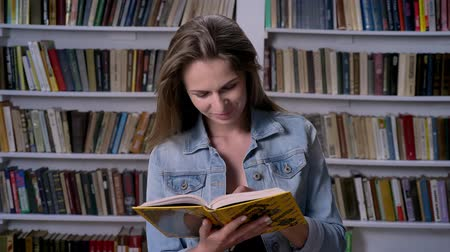 alfabetização : Young cute woman is reading book in library, smiling, bookshelf on backgorund