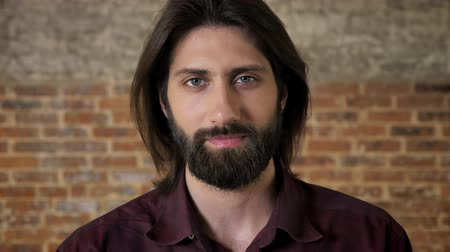 truly : Young nice brunette man with beard is watching at camera, brick background
