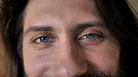 truly : Eyes of young nice brunette man with beard is watching at camera, smiling, brick background Stock Footage